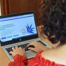 Mujer frente a la computadora con página del coloquio